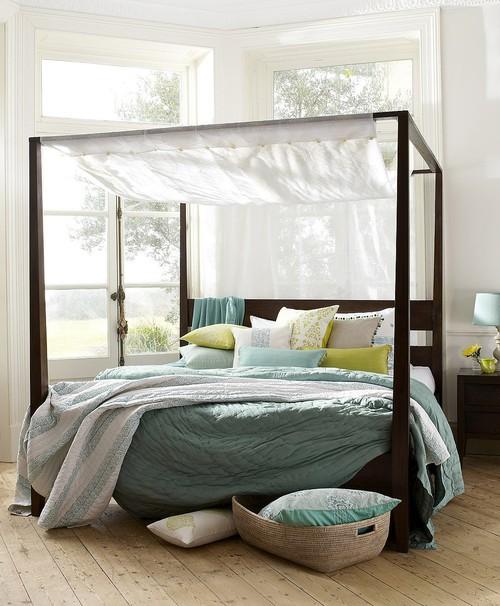 cama con baldaquino cuadrado junto ventanal via justinetaylor